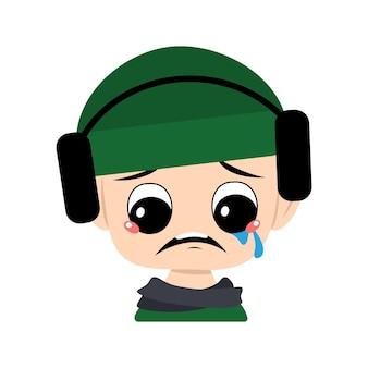 Kind met huilen en tranen emotie verdrietig gezicht depressieve ogen in groene hoed met koptelefoon schattig kind w...