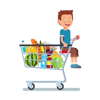 Kind zit in een supermarkt winkelwagentje