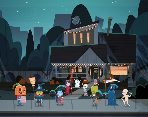 Kinderen die monsterskostuums dragen die in stadstrucs lopen of gelukkig halloween-het concept van de bannervakantie behandelen