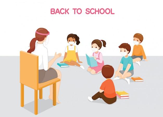 Kinderen dragen chirurgische maskers zittend op de vloer, luisteren vrouwelijke leraar lesgeven, terug naar school, bescherming coronavirusziekte, covid-19