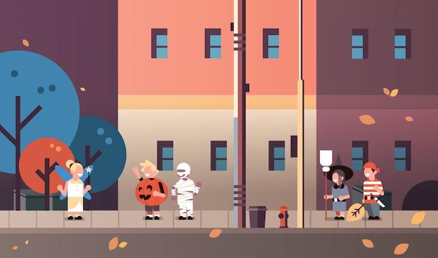 Kinderen dragen monsters fee pompoen piraat mummie heks kostuums wandelen stad achtergrond