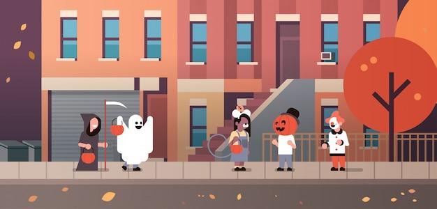 Kinderen dragen monsters geest pompoen tovenaar clown kostuums wandelen stad banner