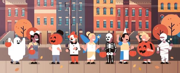 Kinderen dragen monsters kostuums wandelen stad huis gebouwen banner