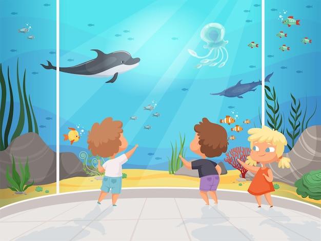 Kinderen in het aquarium. kinderen met leraar in groot watermuseum onderwater verschillende vissen oceaan fauna gelukkige mensen achtergrond.