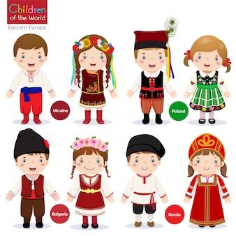 Kinderen in verschillende traditionele kostuums (oekraïne, polen, bulgarije, rusland) Premium Vector