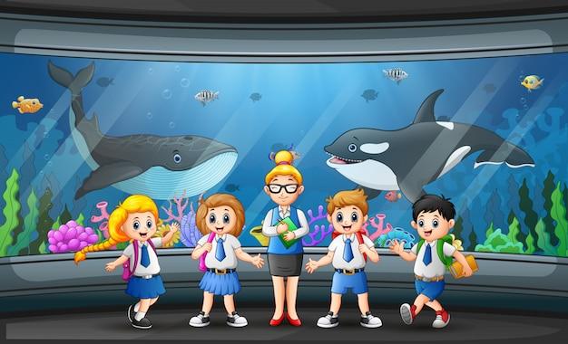 Kinderen kijken naar vissen op aquarium excursie met vrouw leraar