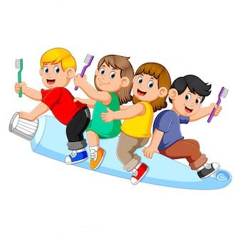 Kinderen rijden op grote tand pasta en houden een tandenborstel