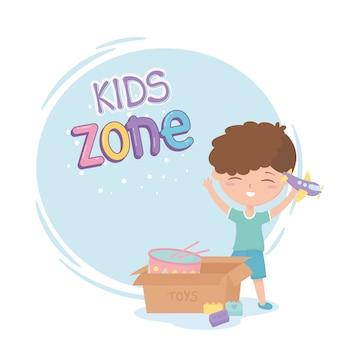 Kinderzone, schattige kleine jongen met vliegtuig en doos met drumspeelgoed