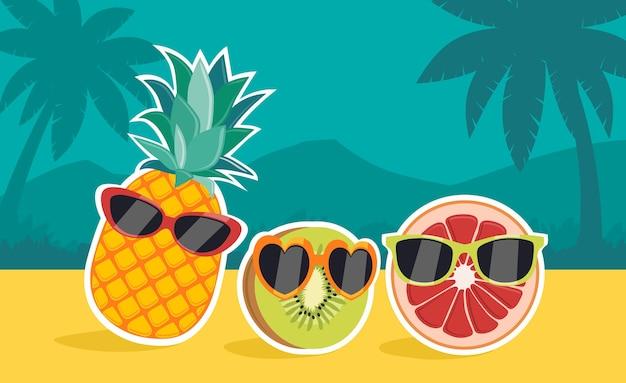 Kiwi en rode sinaasappel (sanguinea) die een bril dragen op het strand met palmbomen op de achtergrond