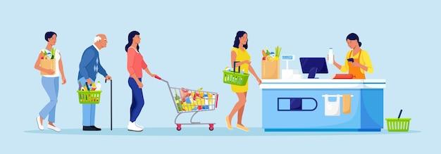 Klanten staan in de rij bij de supermarkt met goederen in het winkelwagentje. vrouw zet aankopen op kassierbureau om te betalen. wachtrij in de winkel. boodschappen kopen
