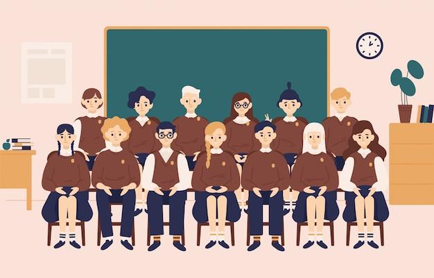 Klasse groepsportret. lachende meisjes en jongens gekleed in schooluniform of leerlingen zitten in de klas tegen schoolbord