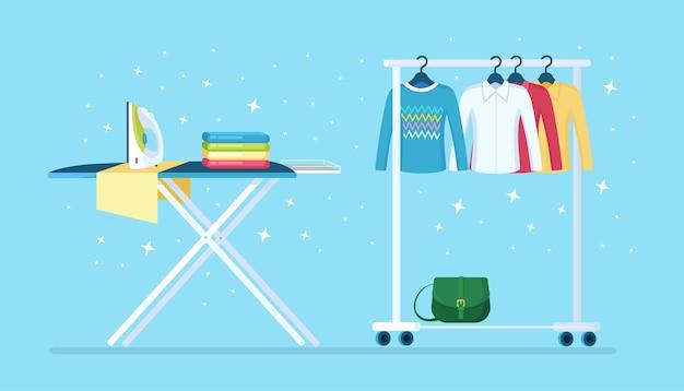 Kledingkast voor dames en strijkplank met strijkijzer. metalen rek met kleding, tassen aan hangers in boetiek. winkelstandaard met modieuze outfit. interieur van kleedkamer
