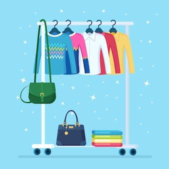 Kledingkast voor vrouw. metalen rek met kleding, tassen aan hangers in boetiek. winkelstandaard met modieuze outfit. interieur van kleedkamer.