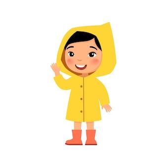 Klein aziatisch meisje in een gele regenjas