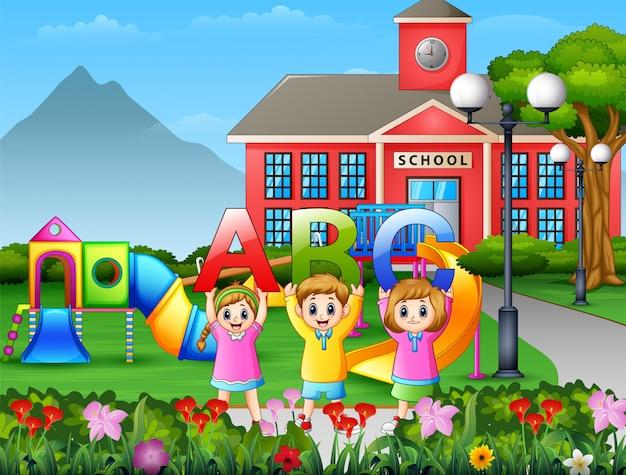 Klein kind houdt abc-brief in het schoolplein