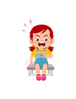 Klein meisje met behulp van mobiele telefoon en boos