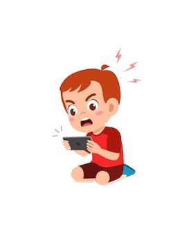 Kleine jongen met behulp van mobiele telefoon en boos