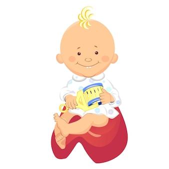 Kleine jongen met een rammelaar in zijn hand glimlachend zittend op het potje