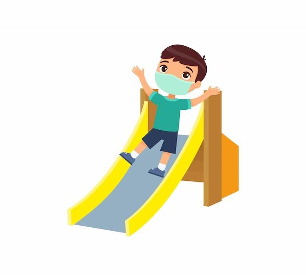 Kleine jongen met gezichtsmasker glijdt van een kinderglijbaan. virusbescherming, allergieënconcept. vakantie en entertainment op de speelplaats. stripfiguur. vlakke afbeelding.