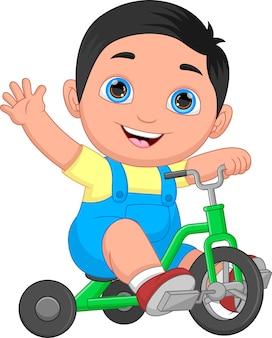 Kleine jongen rijdt op een driewieler en zwaait