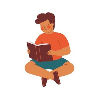 Kleine jongen zit op de vloer en leest met belangstelling een boek.