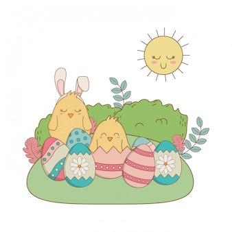 Kleine kuikens met eieren geschilderd in het veld