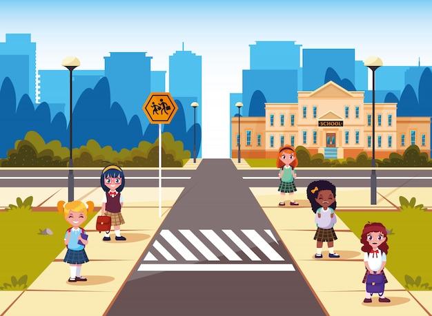 Kleine studenten meisjes voorkant van schoolgebouw