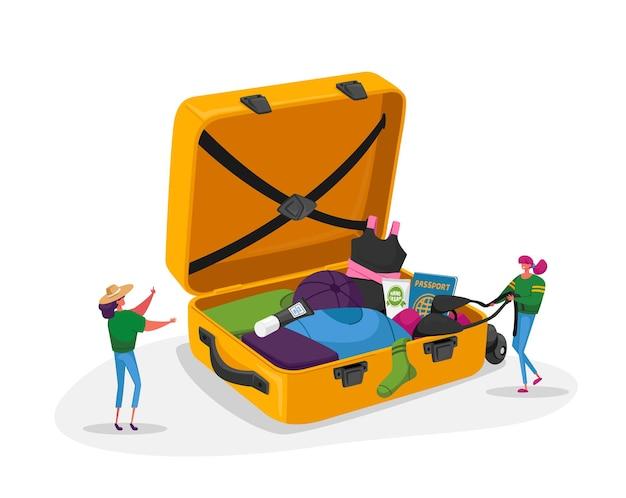Kleine vrouwelijke personages halen reiskleding of accessoires uit de enorme koffer