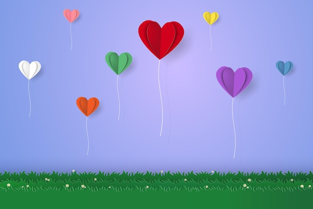 Kleurrijke gevouwen hartballonnen die over gras vliegen in papierkunststijl