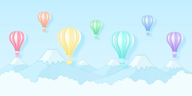 Kleurrijke heteluchtballonnen die over de berg vliegen, regenboogkleurenpatroon, papierkunststijl