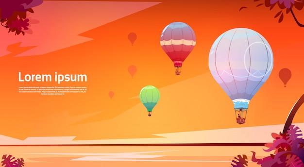 Kleurrijke luchtballons die in hemel over zonsondergang overzees landschap vliegen