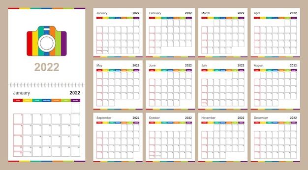 Kleurrijke wandkalender voor 2022 op beige achtergrond, week begint op zondag.