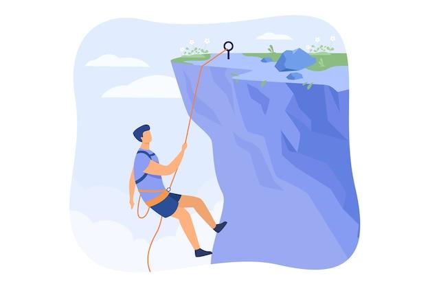Klimmer die aan touw hangt en zich bovenop rotsachtige bergmuur trekt. extreme bergbeklimmer klimmen op klif. voor sport, buitenactiviteiten, risico, alpinistisch concept