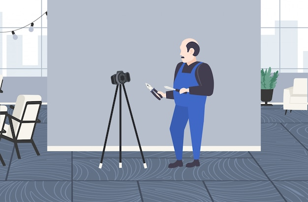 Klusjesman werknemer met schroevendraaier en kniptang blogger opname online video met digitale camera op statief sociaal netwerk blogging concept modern appartement interieur volledige lengte horizontaal
