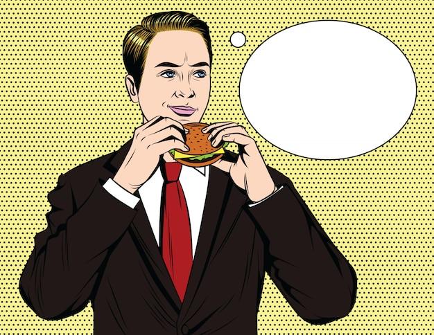 Knappe gelukkige kerel die in kostuum hamburger eet