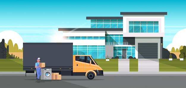 Koerier man in de buurt van bestelwagen met kartonnen dozen wasmachine huishoudelijke apparaten winkel goederen aankoop distributie concept cottage huis exterieur