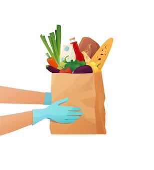 Koeriers gehandschoende hand met een papieren eco-tas met boodschappen. voedsel levering concept.