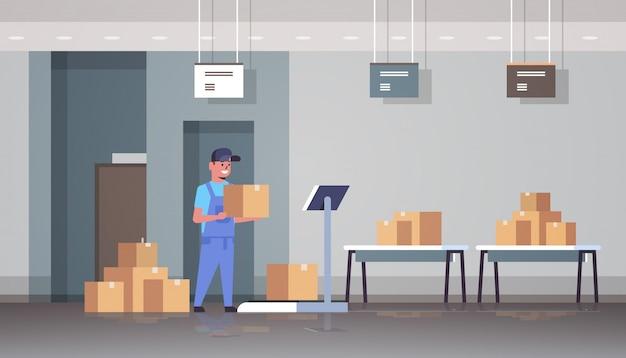 Koeriersmens in het uniform zetten van pakketdoos op schalen post express levering logistieke service concept moderne magazijn interieur