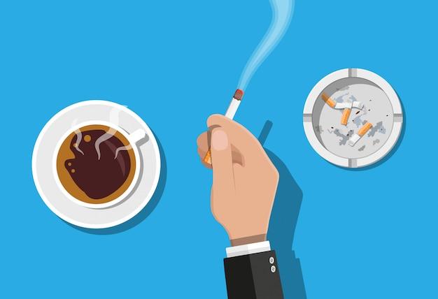 Koffiekopje en asbak vol rook sigaretten.