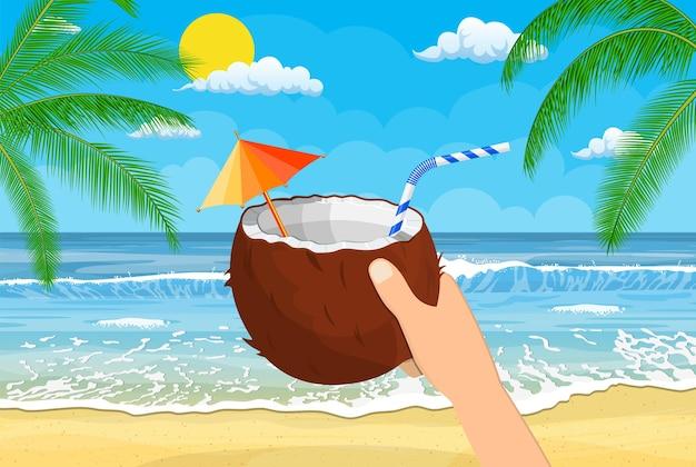 Kokosnoot met koude drank, alcoholcocktail in de hand. landschap van palmboom op strand. zon met weerspiegeling in water, wolken