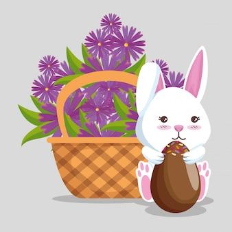 Konijn met chocolade-eieren en bloemen in de mand