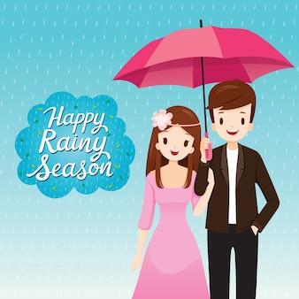 Koppel onder paraplu samen in de regen, ze gelukkig regenseizoen