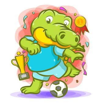 Krokodil schopt de bal voor de kampioen met de trofee naast hem