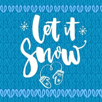 Laat het sneeuwen. inspirerende wintercitaat, borstelbelettering op blauwe gebreide textuur. witte tekst voor kerstkaarten.