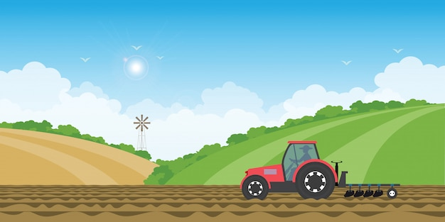 Landbouwer die een tractor in landbouwgrond op landelijke de heuvelachtergrond drijven van het landbouwbedrijflandschap.