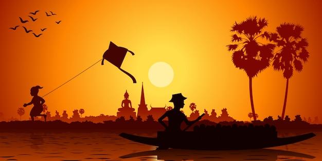 Landleven van aziatische jongens, vliegeren en vissen in een roeiboot