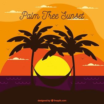 Landschap bij zonsondergang met palmbomen en hangmat