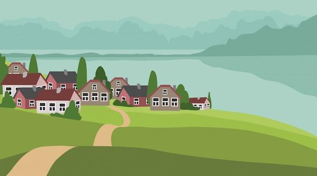 Landschap met groene heuvels, dorp omgeven door bergen en de zee.