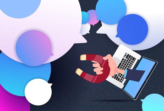 Laptop hand houden magneet nieuw idee chat ondersteuning bellen trekken concept