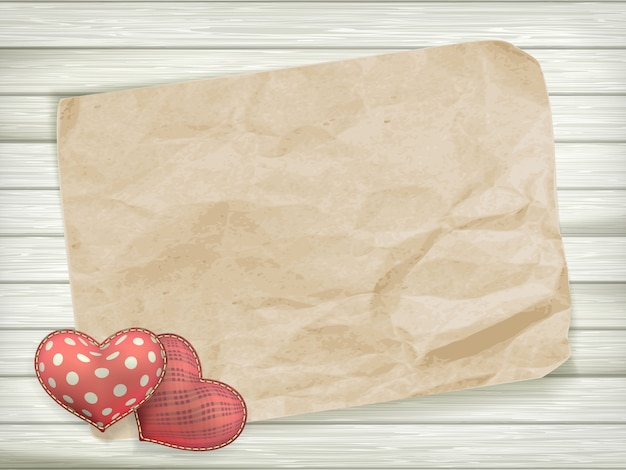 Leeg oud stuk papier en vintage handmaded valentijnsdag speelgoed hart over houten achtergrond.